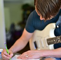 Man with Electric Guitar Writing Music #1